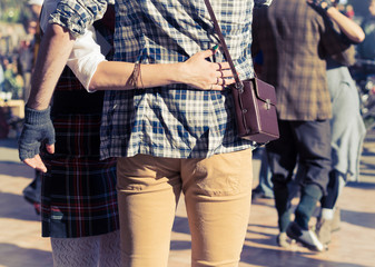 Stylish pair of hipsters embrace on the street, rear view.