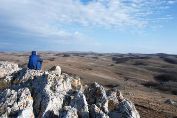 Турист на скале, смотрящий вдаль