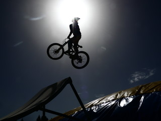 dirtbike bmx rider jumps against sun