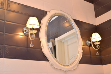Mirror and two sconces in a bathroom. Modern classics with rococ