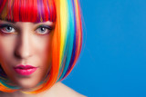 Fototapety beautiful woman wearing colorful wig against blue background