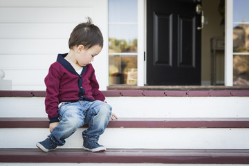 Melancholy Mixed Race Boy Sitting on Front Porch Steps