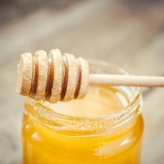 Honey in glass jar and wooden dipper