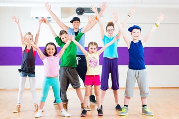 Tanzlehrer gibt Kindern Zumba Fitness in Tanzstudio