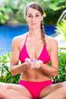 Frau in tropischer Garten macht Yoga am Pool