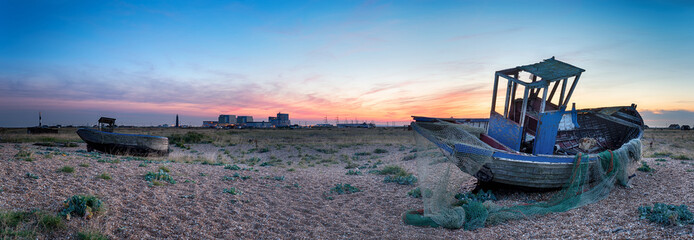 An old wrecked fishing boats at Dungeness in Kent with the two l