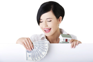 Woman holding a house model and money clip