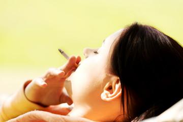 Woman smoking on a hammock