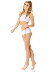 Woman measuring, wearing underwear