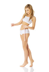 Woman measuring, wearing underwear