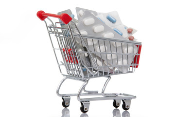 Shopping cart full of pills, isolated on white background