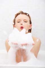 Young woman blowing foam