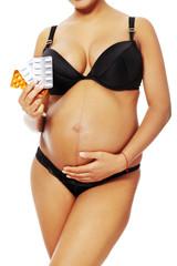Pregnant women holding pills