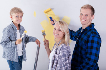 Family painting wall in new house