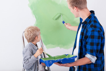 Dad and son painting wall