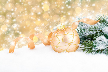 Golden christmas decoration balls with ribbon bow on abstract ba