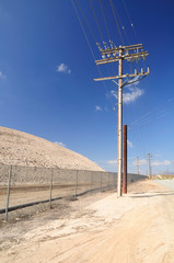 Wooden pylon at the sand road in desolate area. California.