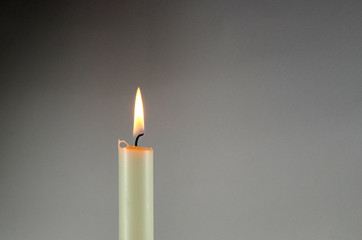 One white candle at grey background