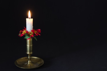 Christmas decorated candle at a black background