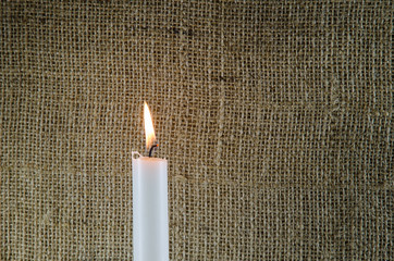 Burning candle with burlap background
