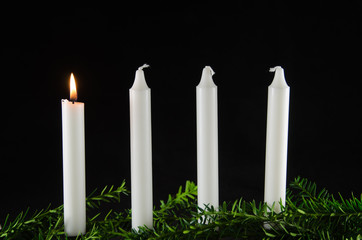 Four advent candles at black background