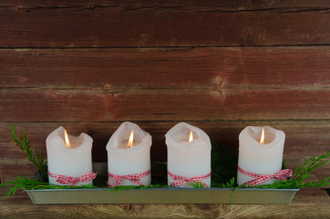 Four advent candles at an old weathered red wall