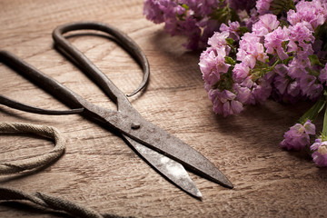 Old Vintage steel scissors on wooden table  with flower