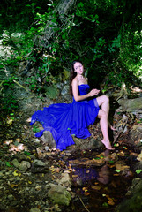 A young girl in a blue dress at the creek