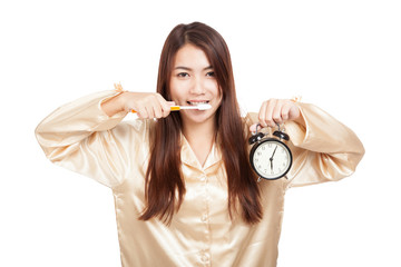 Asian woman in pajamas with toothbrush and clock