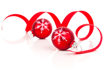 two red christmas decoration balls with satin ribbon, isolated o