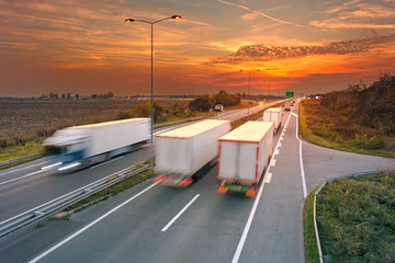 Several trucks in motion blur on highway