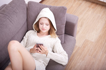 young woman talking to mobile on sofa