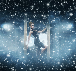 Young and emotional woman in fashion dress over snowy background