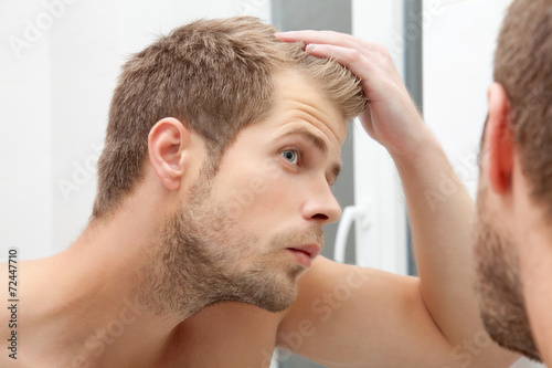Handsome young man worried about hairloss - 72447710