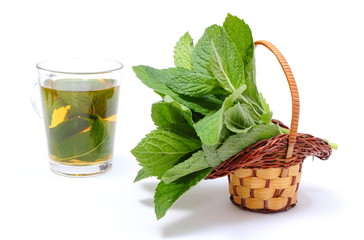 Bunch of fresh green mint in wicker basket and cup of beverage