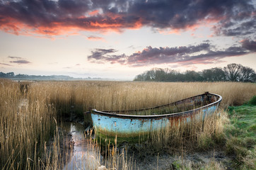 Beautiful sunset over an old rusty fishing boat