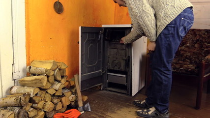 Villager man in sweater light firewood in stove with match