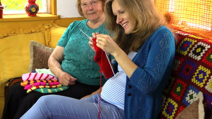 Happy old woman spend time knitting with pregnant granddaughter