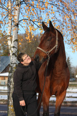 Teenager boy and brown horse portrait in autumn