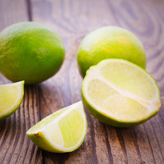 Fresh limes on wooden background.