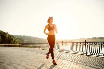 Running woman. Runner jogging in sunny bright light. Female fitn