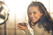 Portrait of happy young woman with cup of hot beverage - 72461572
