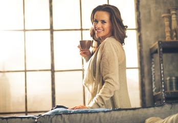 Happy young woman enjoying cup of coffee in loft apartment