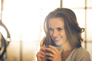 Portrait of smiling young woman with cup of coffee