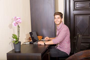 Junger Mann mit Laptop im asiatischen Hotelzimmer
