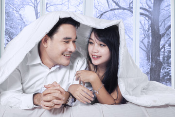 Couple enjoy winter day on bed