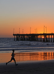 Silhouette of Jogger Running on beach at Sunset, California