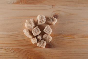 pieces cane sugar on wooden background