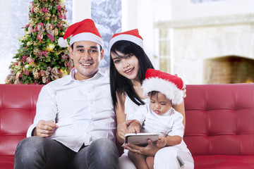Family wearing christmas hat in home