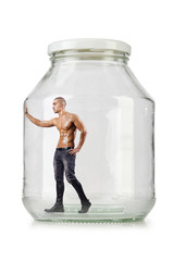 Muscular ripped man in glass jar